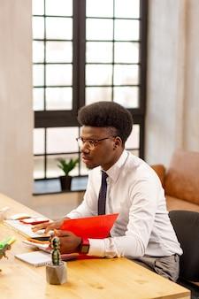 Homem bom e inteligente sentado na mesa do escritório enquanto faz seu trabalho