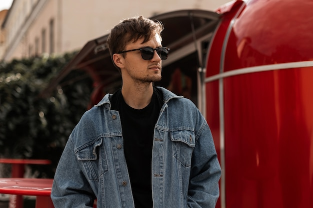 Homem bom elegante jovem hippie em uma jaqueta jeans em uma camiseta preta em óculos de sol com um penteado fica perto de uma van de metal vintage vermelha. o modelo urbano da moda está descansando na cidade. moda de rua.