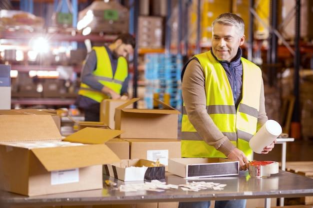 Homem bom trabalhador em pé à mesa e preparando o pacote