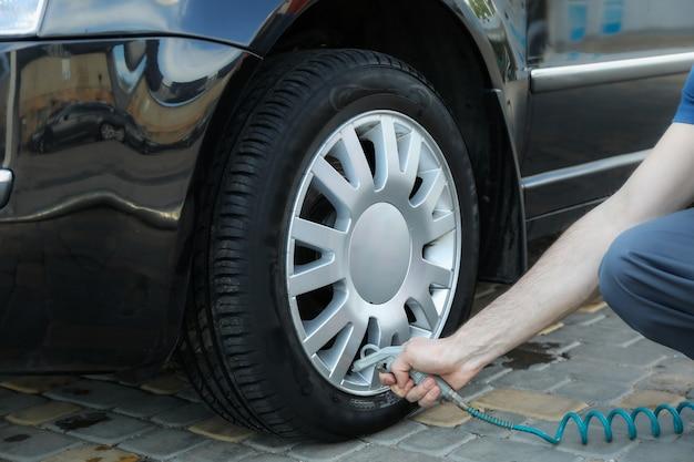 Homem bombeia pneus. inspeção automóvel. manutenção