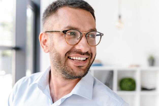 Homem bonito, 30 anos, vestindo camisa branca e óculos, olhando para o lado, em pé perto de uma grande janela no centro de negócios ou sala de escritório