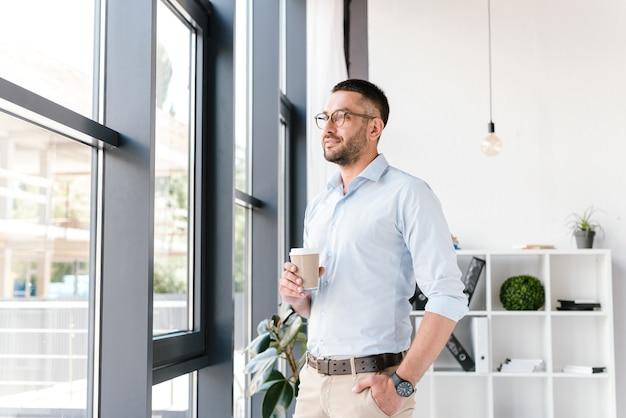 Homem bonito, 30 anos, vestindo camisa branca e óculos, olhando pela janela grande e bebendo café para viagem, enquanto trabalhava no escritório do centro de negócios