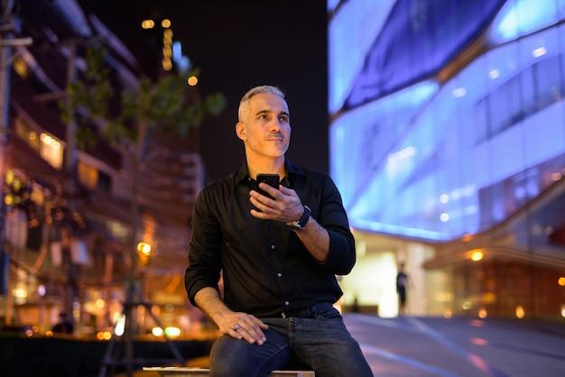 Homem bonito à noite nas ruas usando o celular enquanto pensa