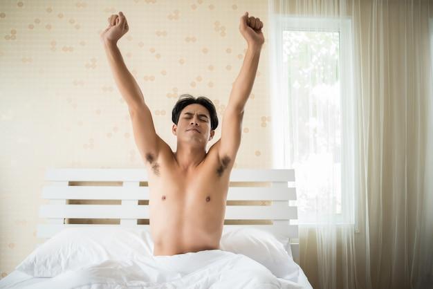 Homem bonito acorda e levantando a mão sobre o ben pela manhã