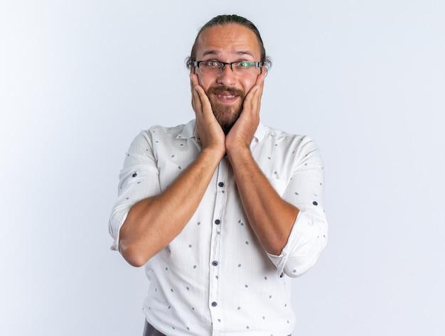Homem bonito adulto animado usando óculos e mantendo as mãos no rosto, olhando para a câmera isolada na parede branca
