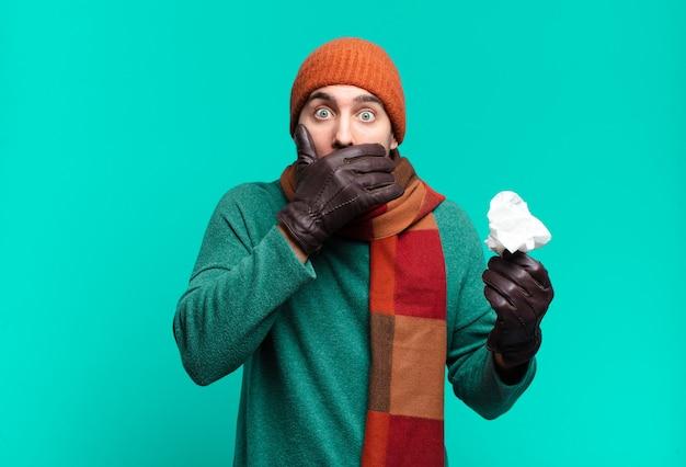 Homem bonito adulto cobrindo a boca com as mãos com uma expressão chocada e surpresa, mantendo um segredo ou dizendo oops. conceito de doença e frio