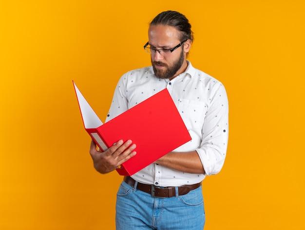 Homem bonito adulto concentrado usando óculos, segurando e olhando para uma pasta aberta
