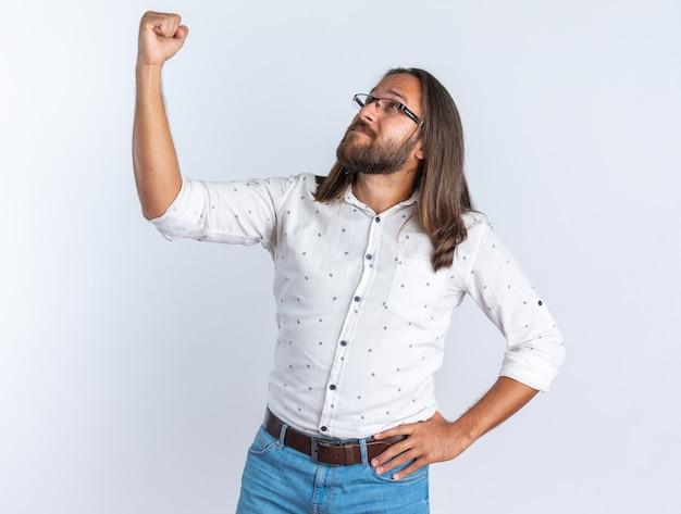 Homem bonito adulto confiante usando óculos, mantendo a mão na cintura, olhando para cima, mostrando o punho isolado na parede branca