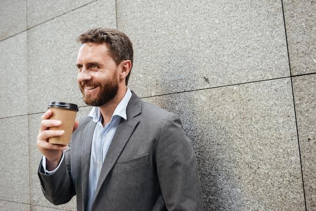 Homem bonito adulto de terno cinza e camisa branca encostado na parede de granito e sorrindo enquanto bebe café para viagem