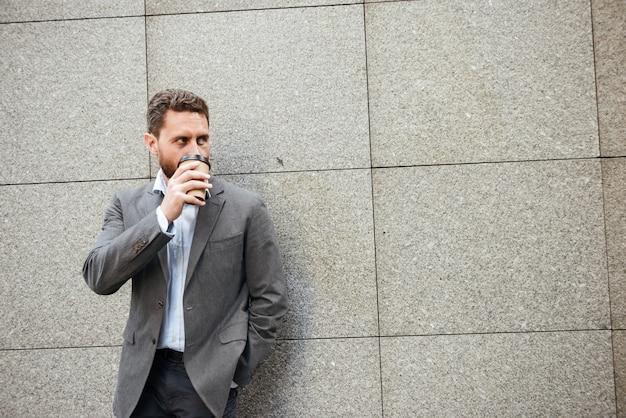 Homem bonito adulto de terno cinza e camisa branca encostado na parede de granito, olhando de lado para copyspace enquanto bebe café para viagem