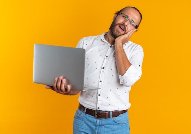 Homem bonito adulto dolorido usando óculos, segurando um laptop e mantendo a mão no rosto, olhando para a câmera isolada na parede laranja