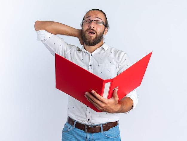 Homem bonito adulto impressionado com óculos, pasta aberta e mão atrás do pescoço