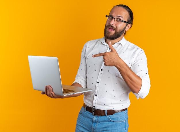 Homem bonito adulto impressionado usando óculos, segurando e apontando para o laptop