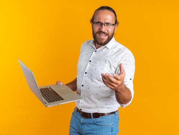 Homem bonito adulto irritado usando óculos, em pé, segurando um laptop e mostrando a mão vazia