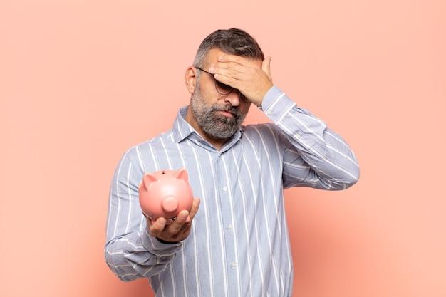 Homem bonito adulto parecendo estressado, envergonhado ou chateado, com dor de cabeça, cobrindo o rosto com a mão