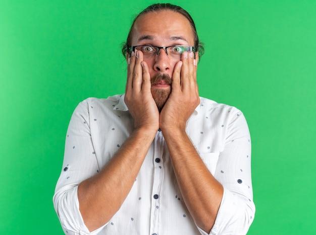 Homem bonito adulto preocupado usando óculos e mantendo as mãos no rosto, olhando para a câmera isolada na parede verde