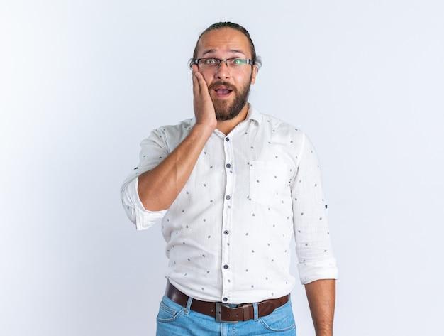Homem bonito adulto preocupado usando óculos, mantendo as mãos no rosto, olhando para a câmera, isolada na parede branca