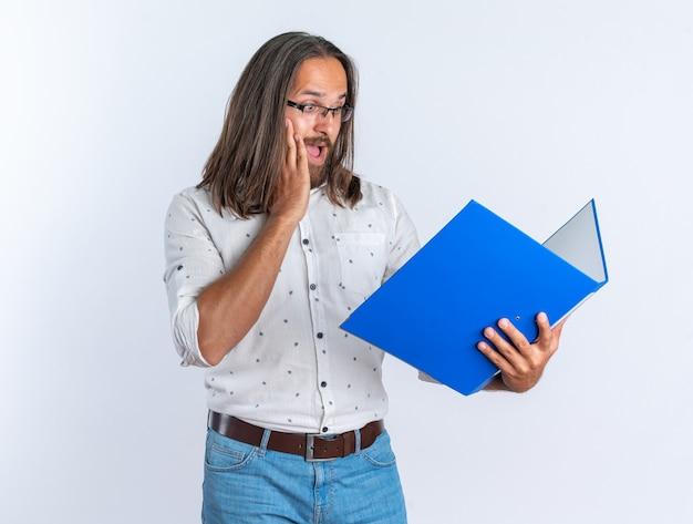 Homem bonito adulto preocupado usando óculos, mantendo as mãos no rosto, segurando e olhando para a pasta