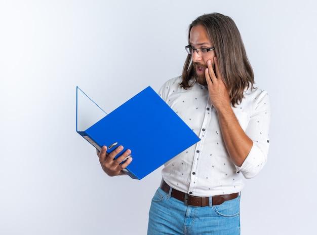 Homem bonito adulto preocupado usando óculos, mantendo as mãos no rosto, segurando e olhando para uma pasta isolada na parede branca
