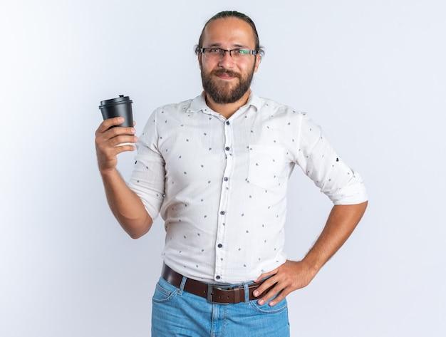 Homem bonito adulto satisfeito usando óculos, mantendo a mão na cintura, segurando uma xícara de café de plástico, olhando para a câmera isolada na parede branca