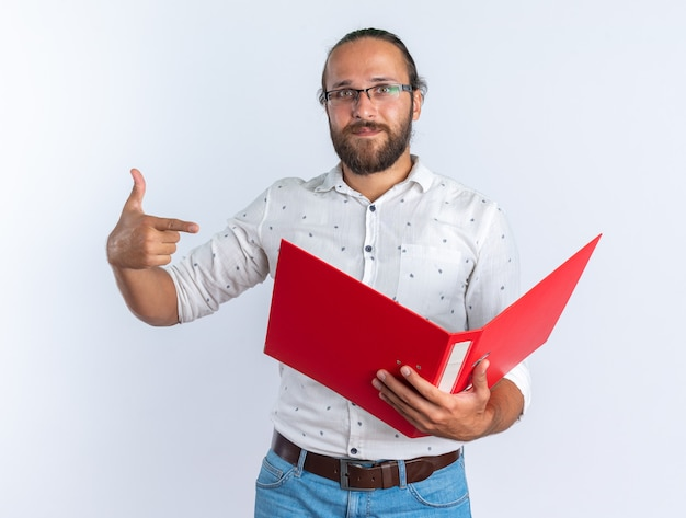 Homem bonito adulto satisfeito usando óculos, segurando e apontando para uma pasta aberta