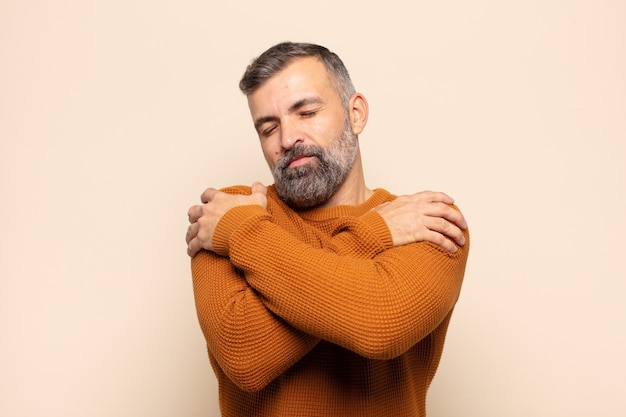 Homem bonito adulto se sentindo apaixonado, sorrindo, se abraçando e se abraçando, permanecendo solteiro, sendo egoísta e egocêntrico