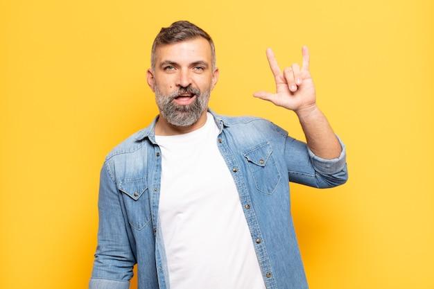 Homem bonito adulto se sentindo feliz, divertido, confiante, positivo e rebelde, fazendo sinal de rock ou heavy metal com a mão