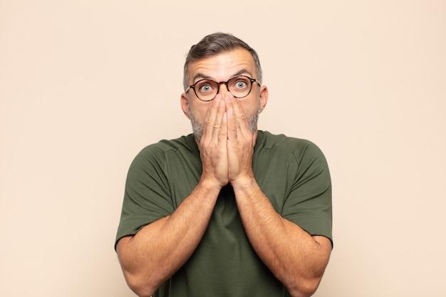 Homem bonito adulto se sentindo preocupado, chateado e com medo, cobrindo a boca com as mãos, parecendo ansioso e tendo bagunçado