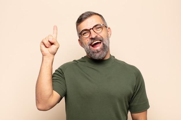 Homem bonito adulto se sentindo um gênio feliz e animado depois de realizar uma ideia, levantando o dedo alegremente, eureka!