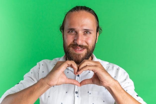 Homem bonito adulto sorridente olhando para a câmera fazendo sinal de amor isolado na parede verde