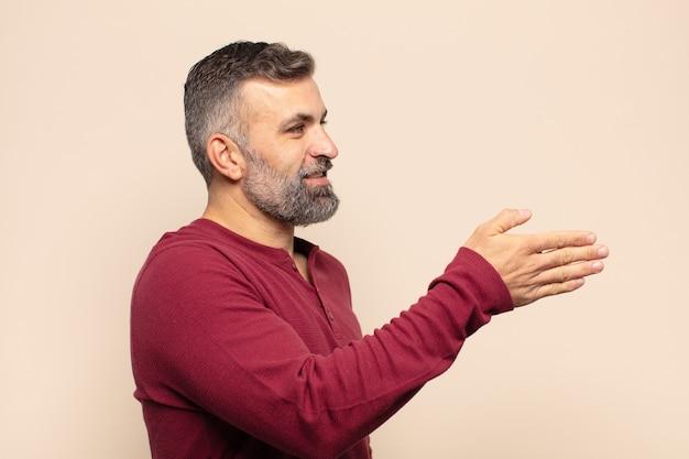 Homem bonito adulto sorrindo, cumprimentando você e oferecendo um aperto de mão para fechar um negócio de sucesso, conceito de cooperação