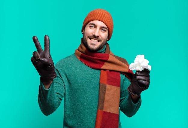 Homem bonito adulto sorrindo e parecendo feliz, despreocupado e positivo, gesticulando vitória ou paz com uma mão. conceito de doença e frio