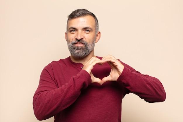 Homem bonito adulto sorrindo e se sentindo feliz, fofo, romântico e apaixonado, fazendo formato de coração com as duas mãos
