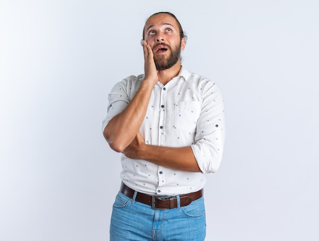 Homem bonito adulto surpreso usando óculos, mantendo a mão no rosto, olhando para cima, isolado na parede branca com espaço de cópia