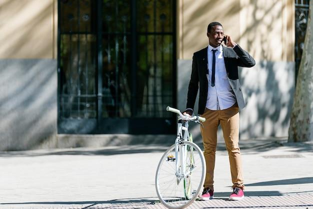 Homem bonito africano com telefone celular e bicicleta de engrenagem fixa na rua.