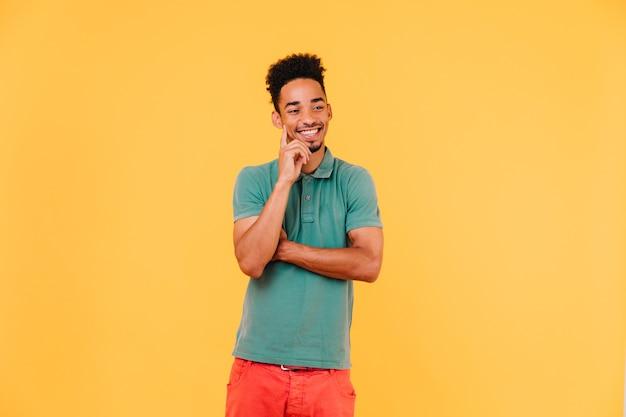 Homem bonito africano pensando em algo com um sorriso. foto interna do cara negro positivo expressando boas emoções.