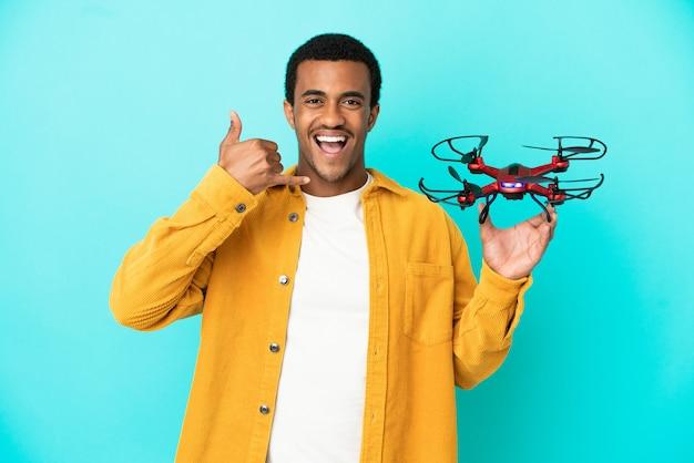 Homem bonito afro-americano segurando um drone sobre fundo azul isolado, fazendo gesto de telefone. ligue-me de volta sinal