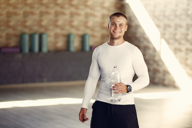 Homem bonito água potável no ginásio