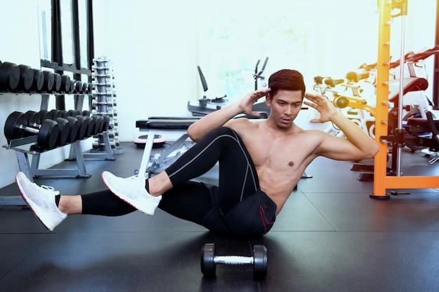 Homem bonito ajuste fazendo abdominais no ginásio