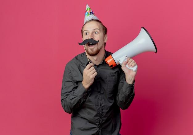 Homem bonito alegre com boné de aniversário segurando um alto-falante e bigode falso em um palito isolado na parede rosa