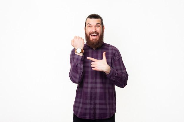 Homem bonito alegre com camisa quadriculada apontando para o relógio