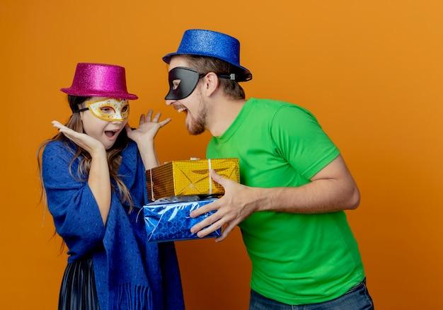 Homem bonito alegre com chapéu azul e máscara de máscara, segurando caixas de presente, olhando para uma jovem surpresa com chapéu rosa e máscara de máscara, levantando as mãos olhando para as caixas