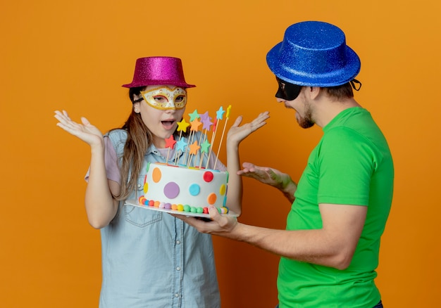 Homem bonito alegre com chapéu azul usando máscara de máscara, segurando um bolo de aniversário, olhando para uma jovem surpresa com chapéu rosa e máscara de máscara, levantando as mãos olhando para o bolo