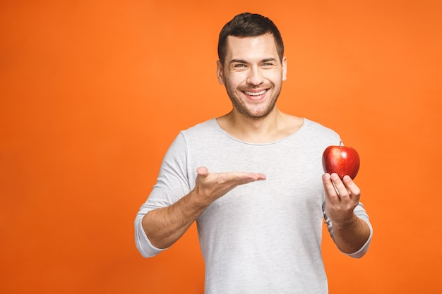 Homem bonito alegre comendo maçã, isolado sobre fundo laranja