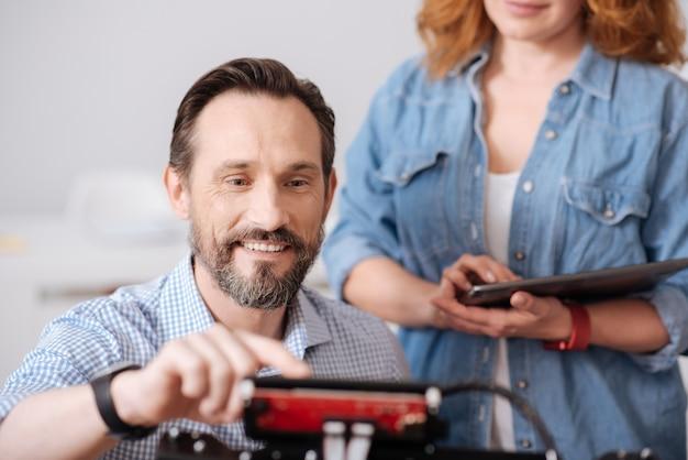 Homem bonito alegre e encantado sorrindo e pressionando um botão enquanto faz a impressão 3d