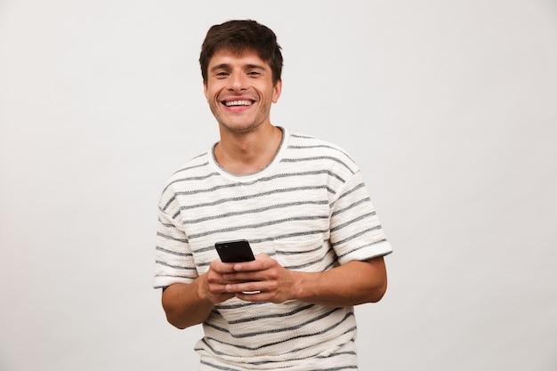 Homem bonito alegre feliz isolado na parede branca usando telefone celular.