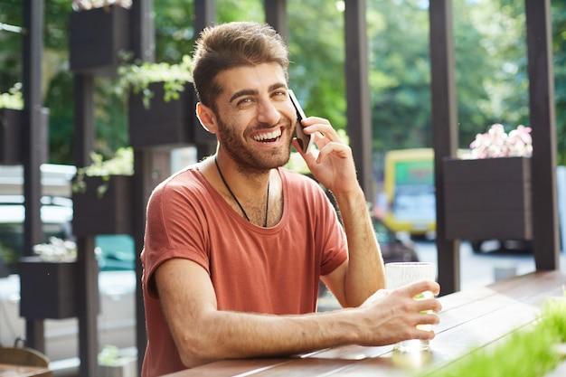 Homem bonito alegre rindo e sorrindo enquanto fala no celular em um café ao ar livre