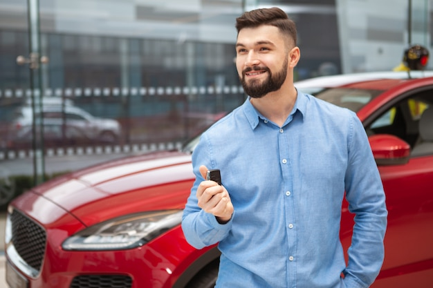 Homem bonito alegre sorrindo, olhando para longe, segurando as chaves de seu automóvel novo na concessionária