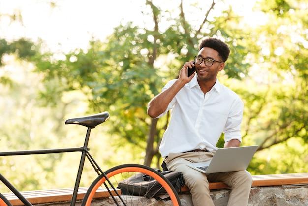 Homem bonito alegre usando computador portátil falando por telefone.