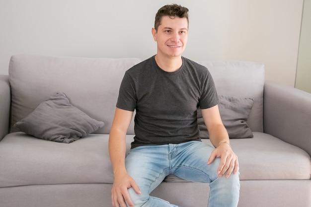 Homem bonito alegre vestindo jeans e camiseta casual, sentado no sofá em casa, mantendo as mãos no colo, olhando para longe e sorrindo. conceito de retrato masculino